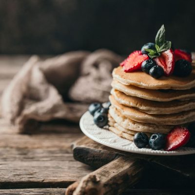 American pancakes with fresh berry on wood background. Summer homemade breakfast.